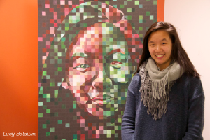 "Chloe So '15 poses next to her ""Chuck Close inspired self portrait."""