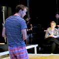 The cast rehearses a water scene in the Black Box.