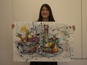 Rachel Yao '16 holding her painting for the Draw Disability contest.  Photo Credit: Gwyneth Hochhausler.