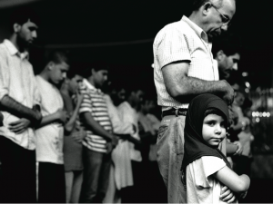 """""""Young Girl Praying with Her Father,"""" Muslim American Society, Brooklyn, NY, 2010. All Images © Robert Gerhardt. Gerhardt created this photo series to """"encourage a dialogue between Muslims and non-Muslims in America that attempts to erase the boundaries that engender a sense of 'them' and begin to foster a sense of 'us.'"""""""