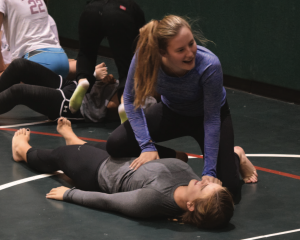 Lilley Salmon '18 practices a Jiu Jitsu take down she had just learned on Siclair Seeligson '18. Credit: Will Briskin