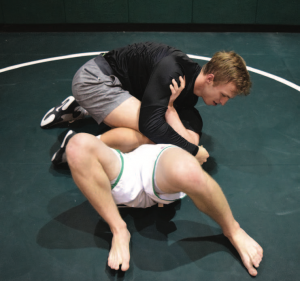 Griffin Thomas '17 practices a choke hold during the club's friday night meeting. Credit: Will Briskin